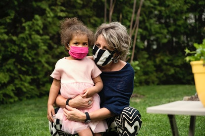 A grandmother holds her granddaughter. Both wear masks during the Covid-19 pandemic.