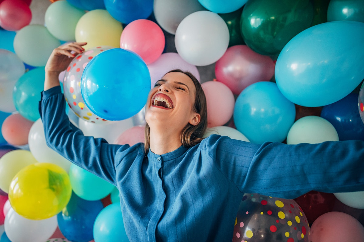 Happy young woman in front of a balloon wall, celebrating her birthday alone.