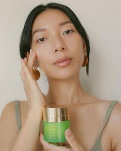 tata harper model applying moisturizer