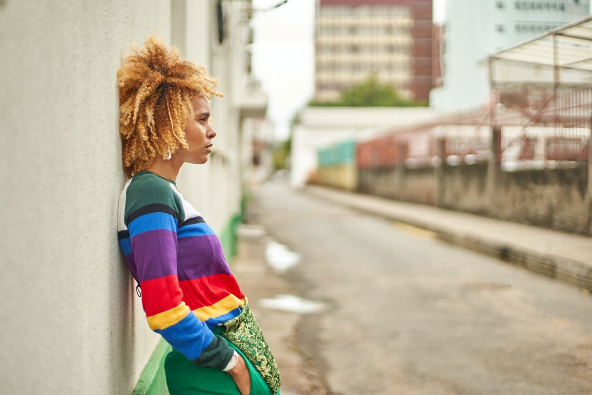 Young woman in a rainbow sweater leaning against a wall, showing her most secret fear, per her zodiac sign.