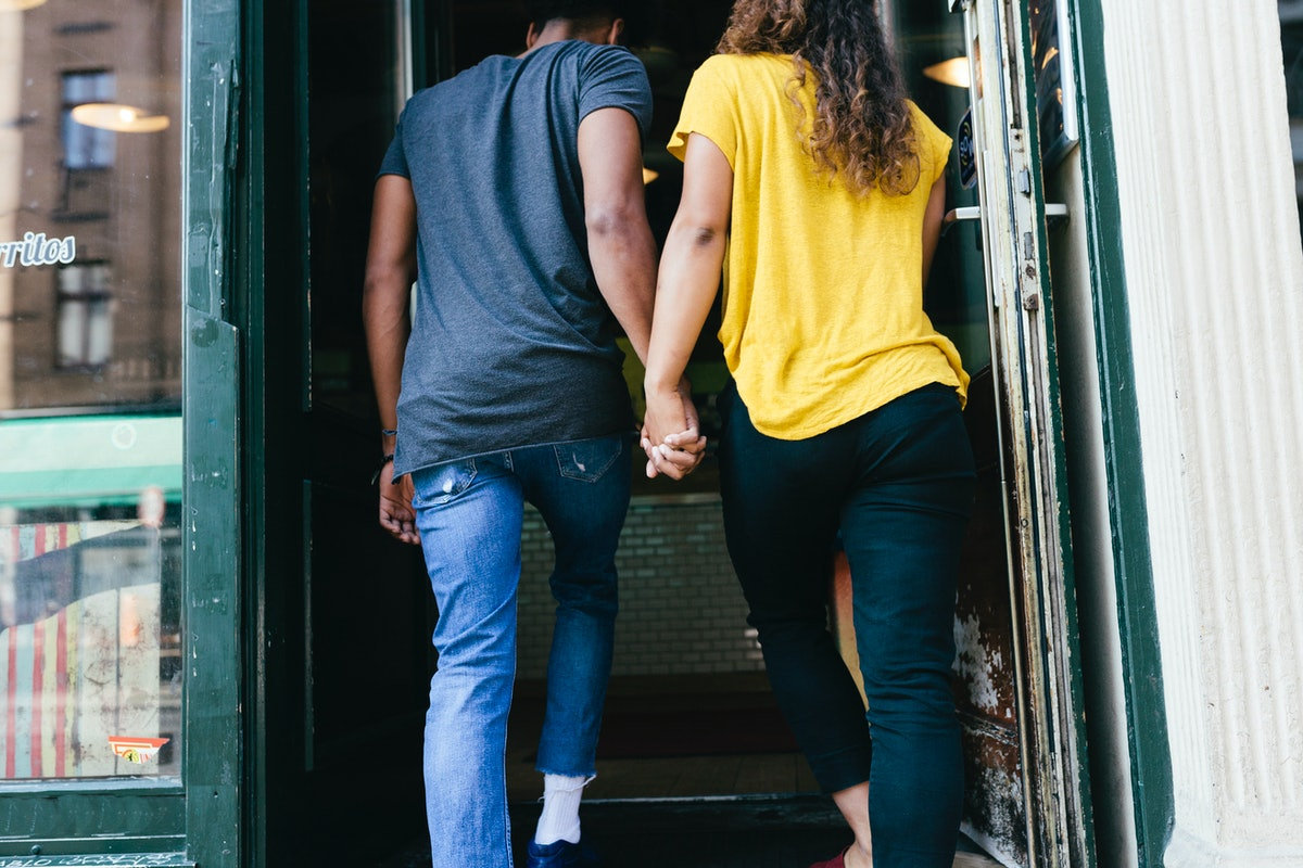 Young woman holding hands with the Aquarius man she's dating as they enter a restaurant.