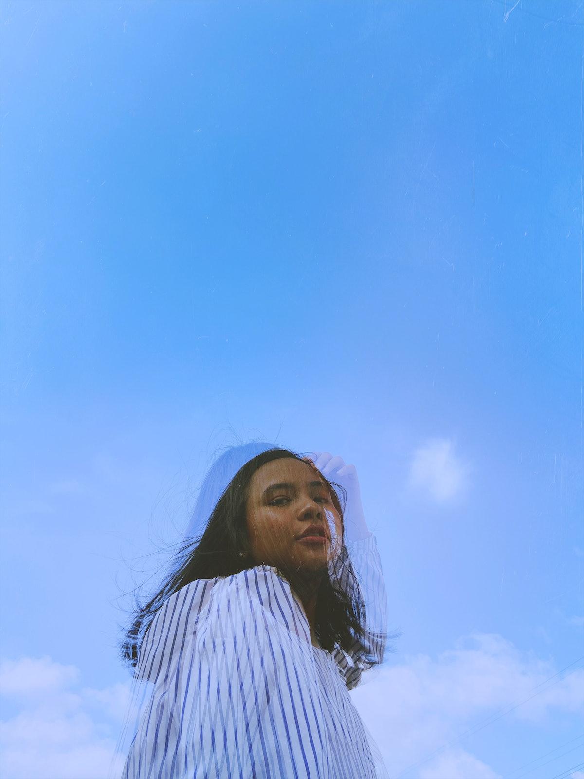 Young misunderstood Aquarius woman against a blue sky.