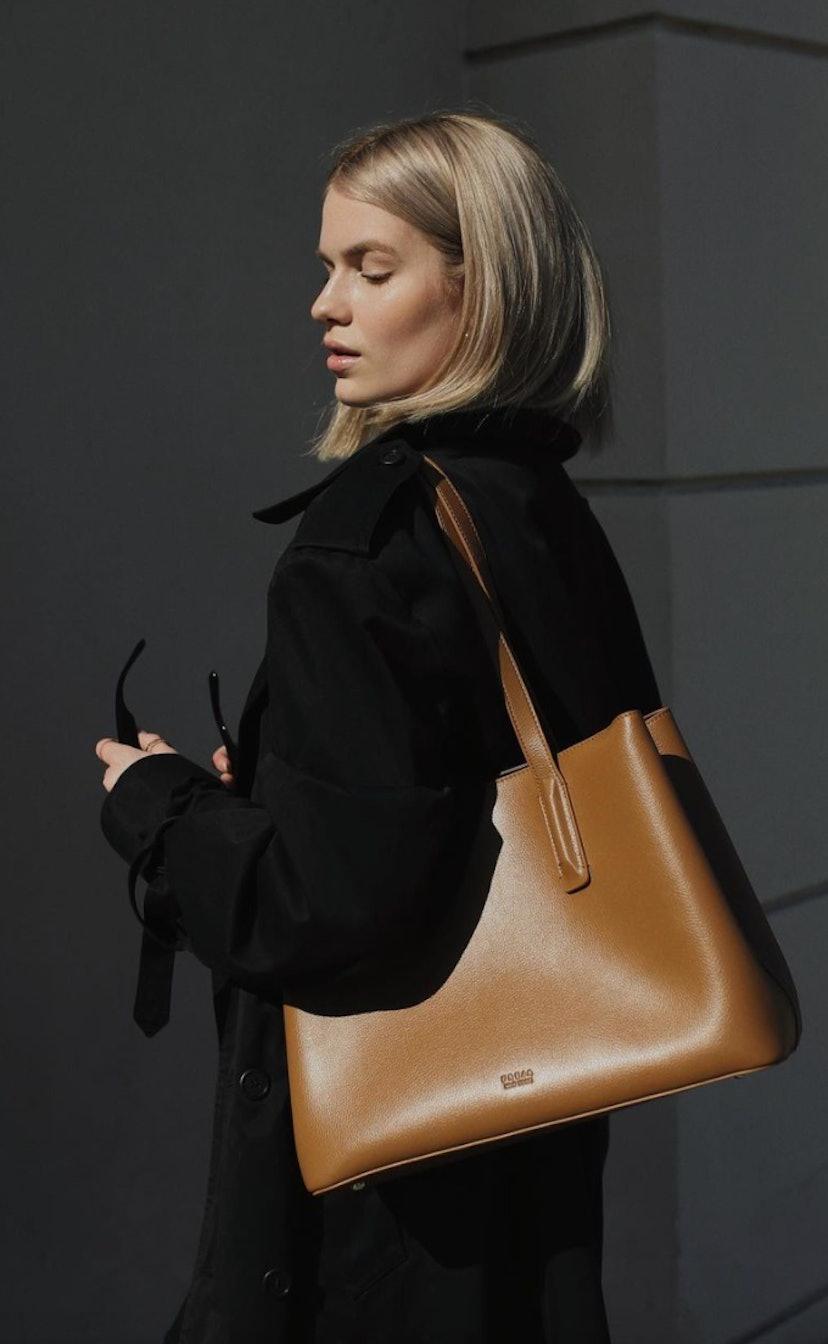 A woman wearing a stylish Freja New York laptop bag.