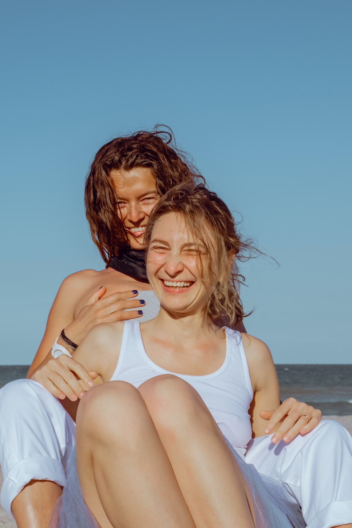 2 sisters smiling and hugging at the beach before posting on Instagram with a comment on sister pic.