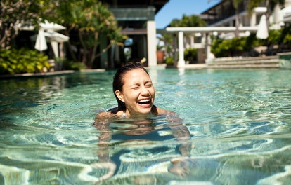 Young woman laughing in a pool before posting a pic on Instagram with pool quotes & captions.