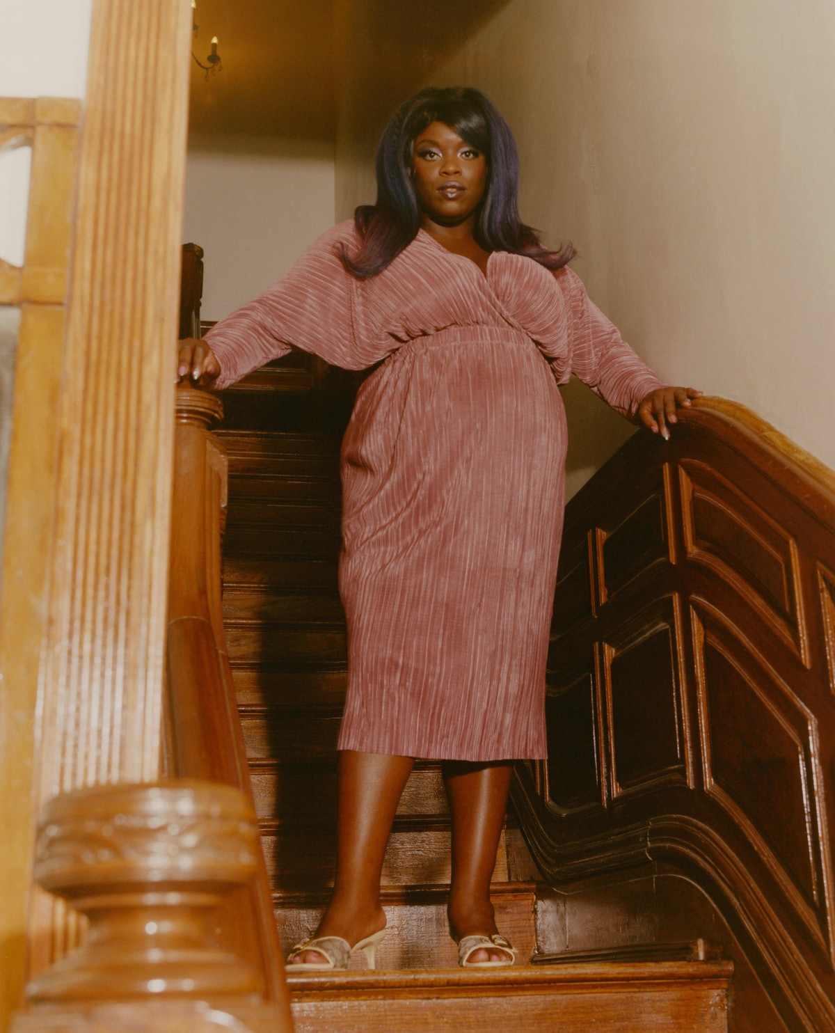 yola stands on a staircase in a pink pleated dress