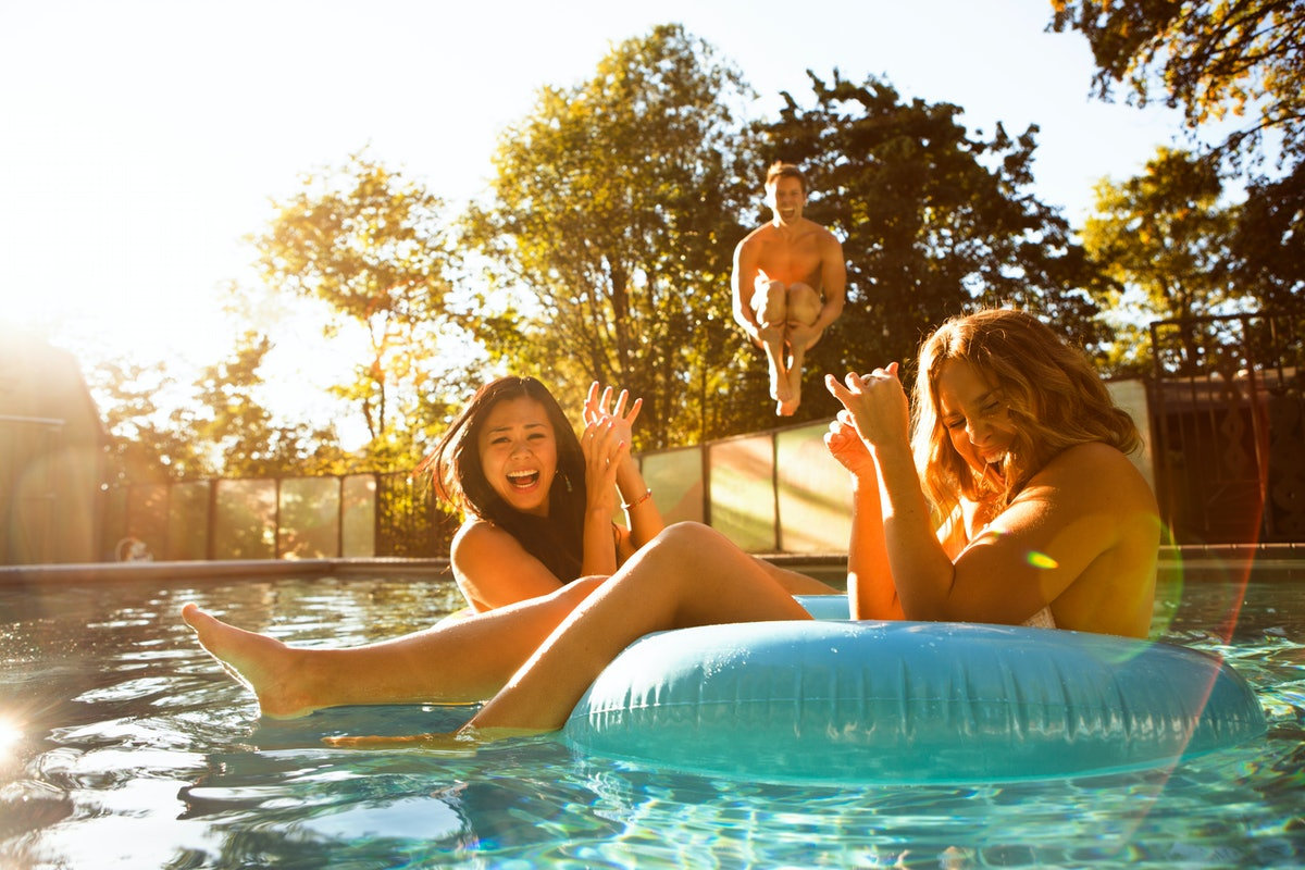 3 friends playing in the pool in the summer before posting on Instagram with pool quotes, pool captions.
