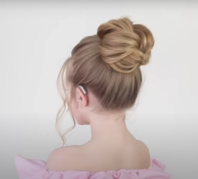 Back-side view of little girl with messy bun high on her head