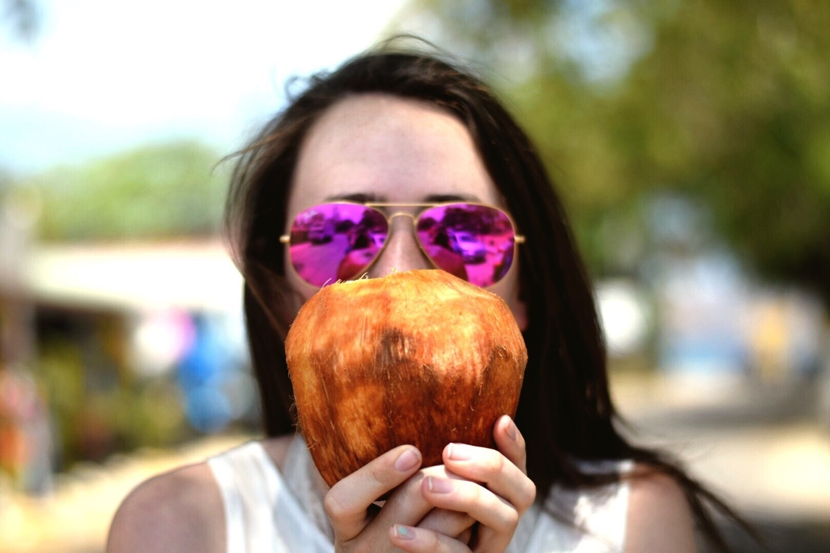 Young woman with pink sunglasses, holding a coconut before posting on Instagram with coconut puns, coconut quotes, coconut tree quotes.