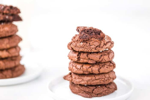chocolate brownie cookies stacked on a white plate, with bites taken out of the top cookie