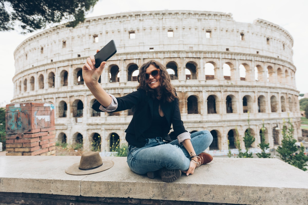 Young traveller with travel bio on her Instagram, taking a selfie in front of the Colosseum in Rome.