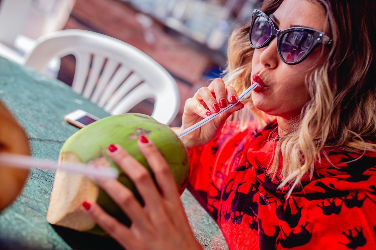 Young woman sipping out of a coconut before posting on Instagram with coconut puns, coconut quotes, coconut tree quotes