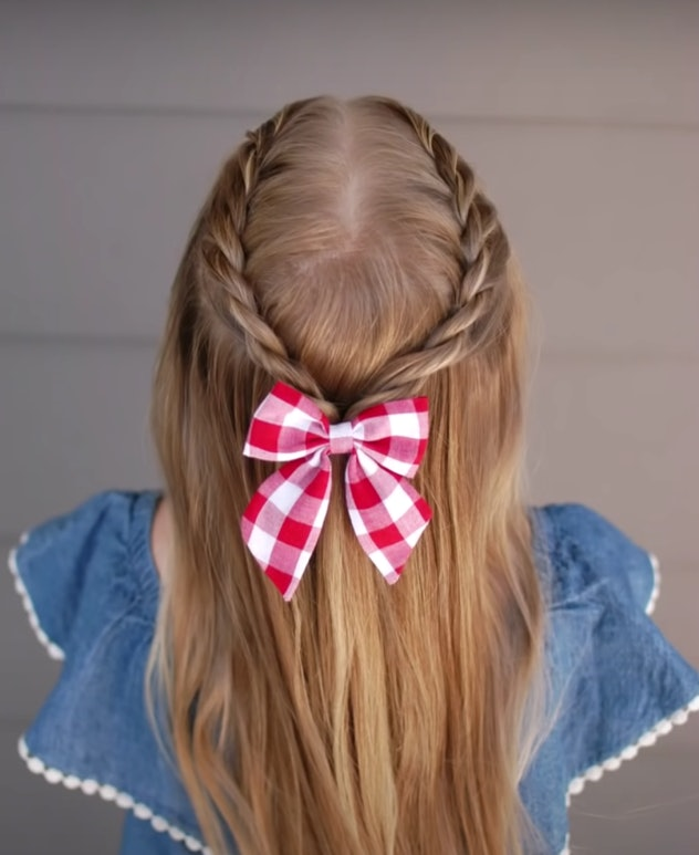 Back of little girl's head, half up style hair with rope braid and red and white gingham bow