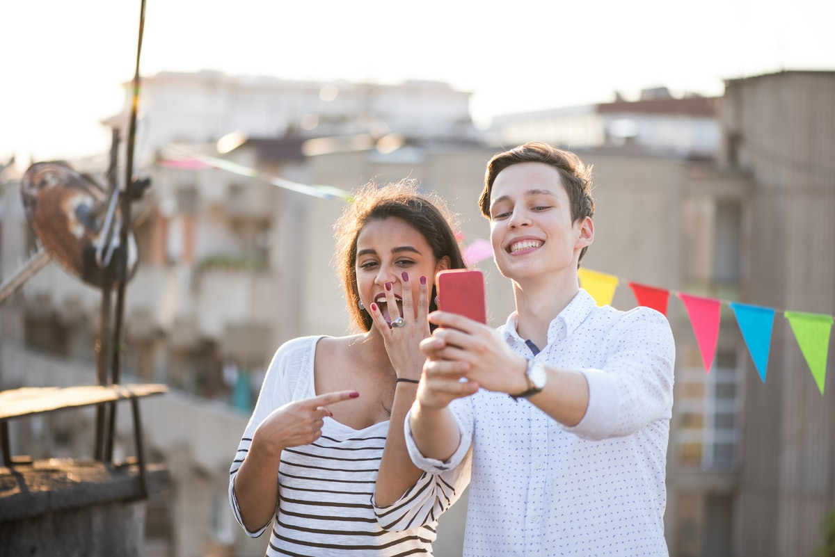 Young couple taking a selfie of bride's engagement ring before posting a wedding countdown quote, caption on Instagram.