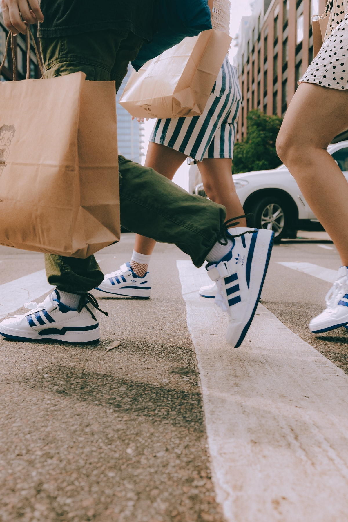 A group of women walking across the street, all of them wearing blue and white Adidas Forum Low snea...