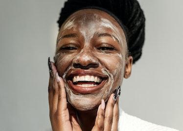 Smiling woman washing her face