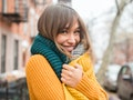 Flirty young woman wearing a sweater and a scarf before posting a pic on Instagram with a flirty cap...