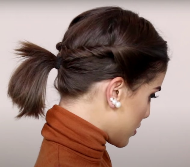 Side view of a woman with short hair pulled back in a ponytail with twists
