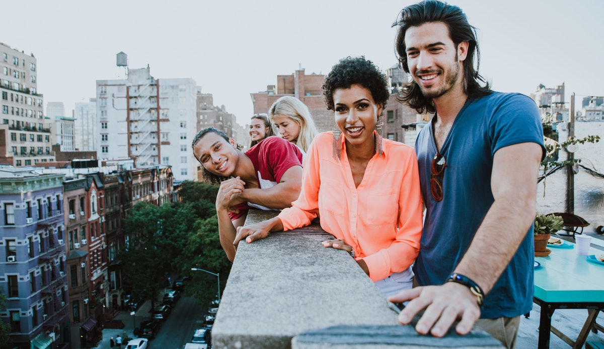 A group of friends smiling for the camera on the roof of someone's apartment, in need of rooftop Instagram captions.