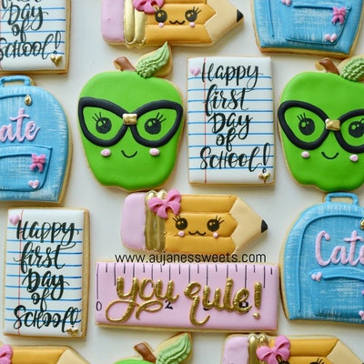 sugar cookies decorated to look like apples, rulers, notebooks and more