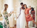 Young bride trying out her wedding dress, taking a selfie with her friend before posting on Instagra...