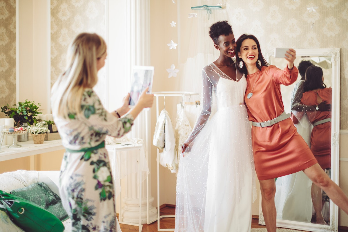 Young bride trying out her wedding dress, taking a selfie with her friend before posting on Instagram with a wedding countdown quote, Instagram caption.