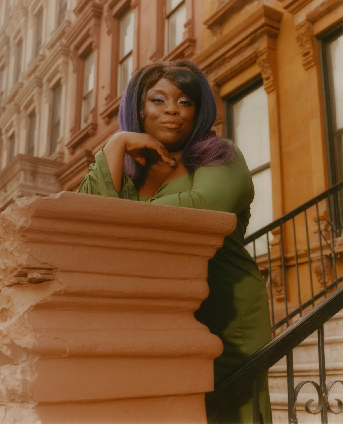 Yola stands on a stoop in a green dress