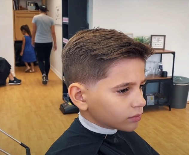 Little boy in barber chair with freshly cut hair swooped to the side