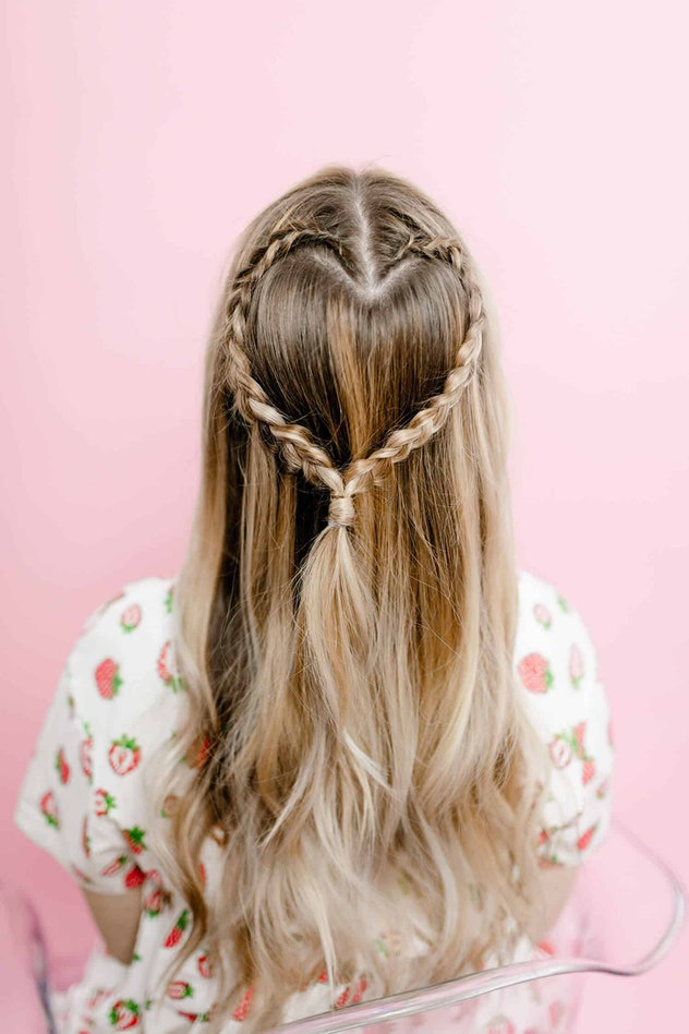Back view of a person with long hair with half-up braid styled in the shape of a heart