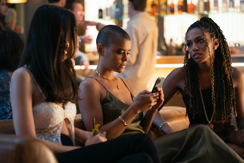 Characters from Gossip Girl sit on a couch at a club. Of the three girls, Julien in the middle is lo...