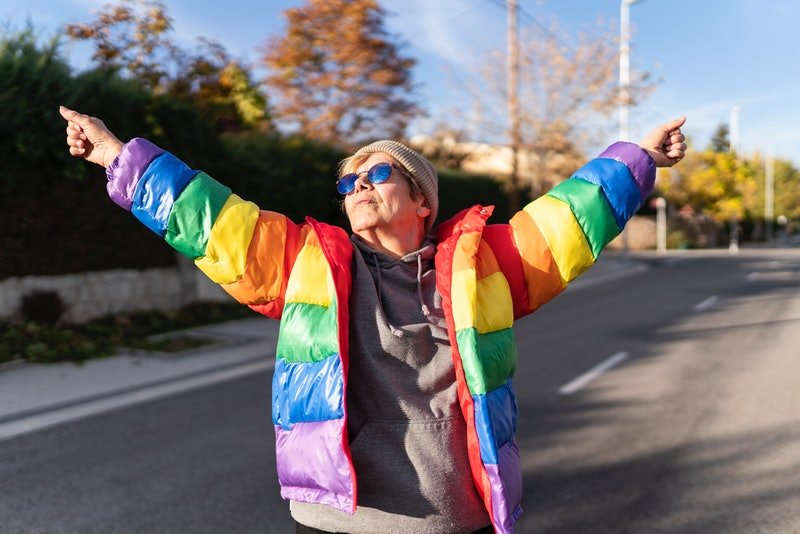 Woman in rainbow coat posing in the middle of the street.