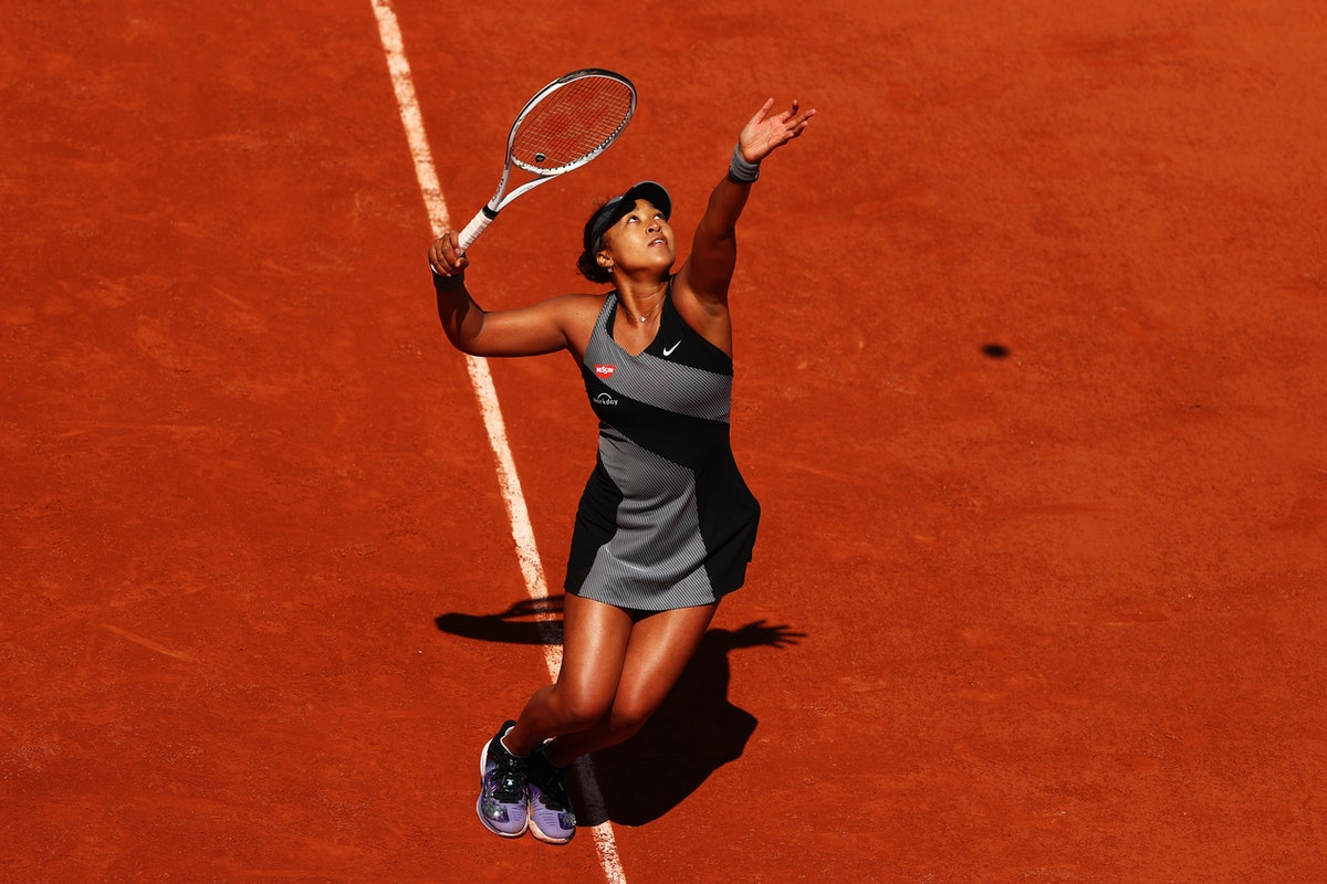 Naomi Osaka of Japan serves in her First Round match against Patricia Maria Tig of Romania during Da...