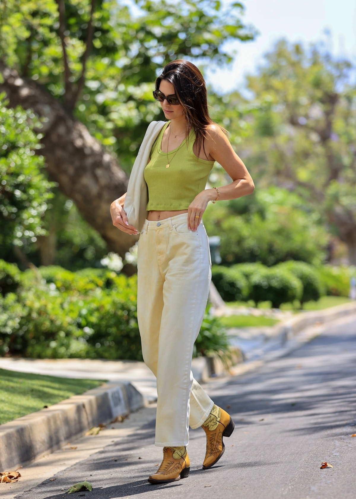 Kendall Jenner wears a green crop top, white jeans, and cowboy boots.