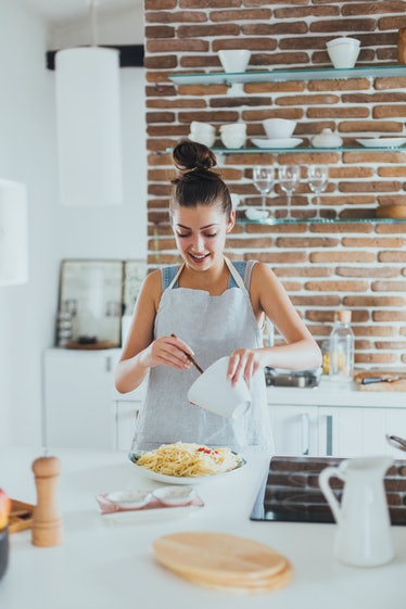 Young woman making TikTok's oven baked pasta recipes in her kitchen.