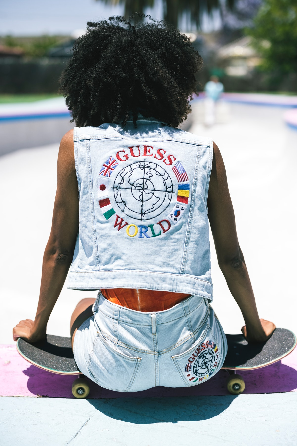 A Black woman with natural hair wearing a light wash denim jacket with a Guess World graphic from it...