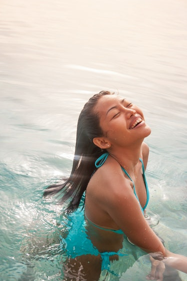 Smiling young woman soaking up the sun's rays, having the best week of August 9, 2021, per her zodia...