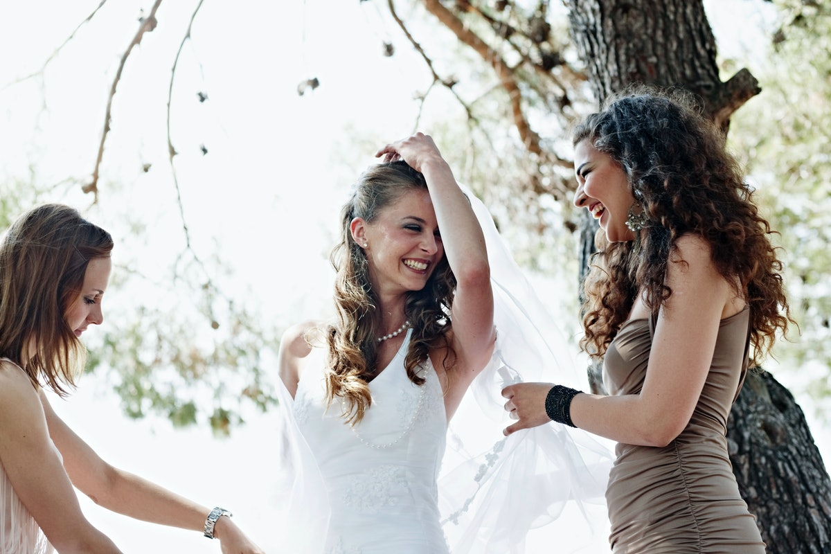 Young bride dancing with her bridesmaids before posting a pic on Instagram with wedding captions.