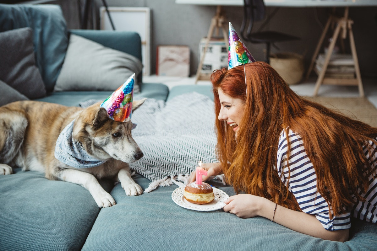 Young woman celebrating her puppy's birthday with a cake and dog birthday Instagram captions.