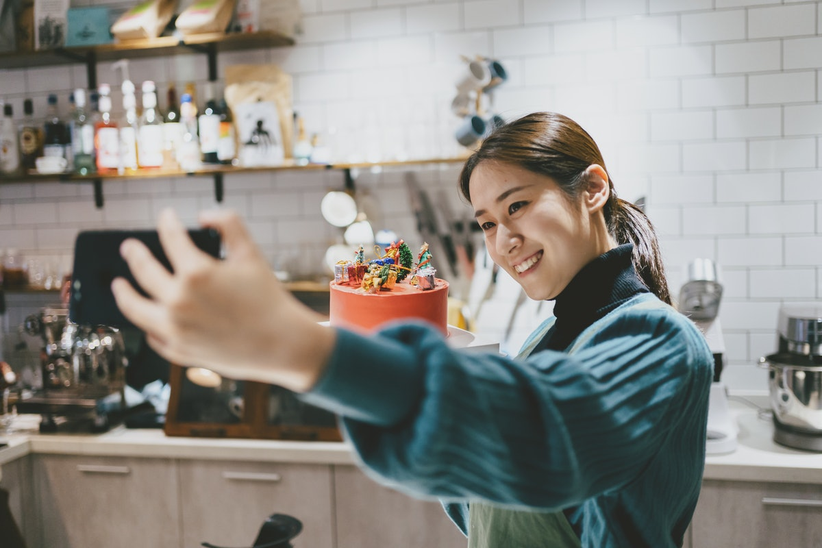 Young woman taking a selfie with her cake before posting on Instagram with birthday cake quotes, cap...