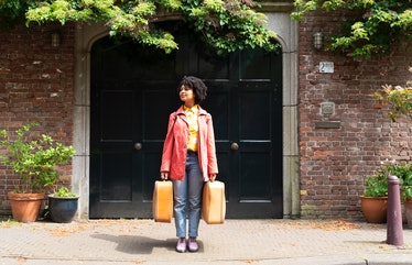 Young woman holding two suitcases, ready to post a pic with travel captions for Instagram.