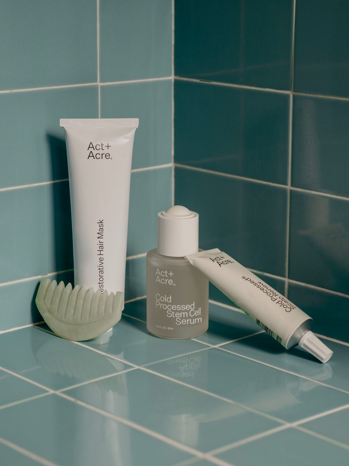 A still life product photo of Acte+Acre's Cold Processed Stem Stell Serum for hair and scalp alongside two other Act+Acre products