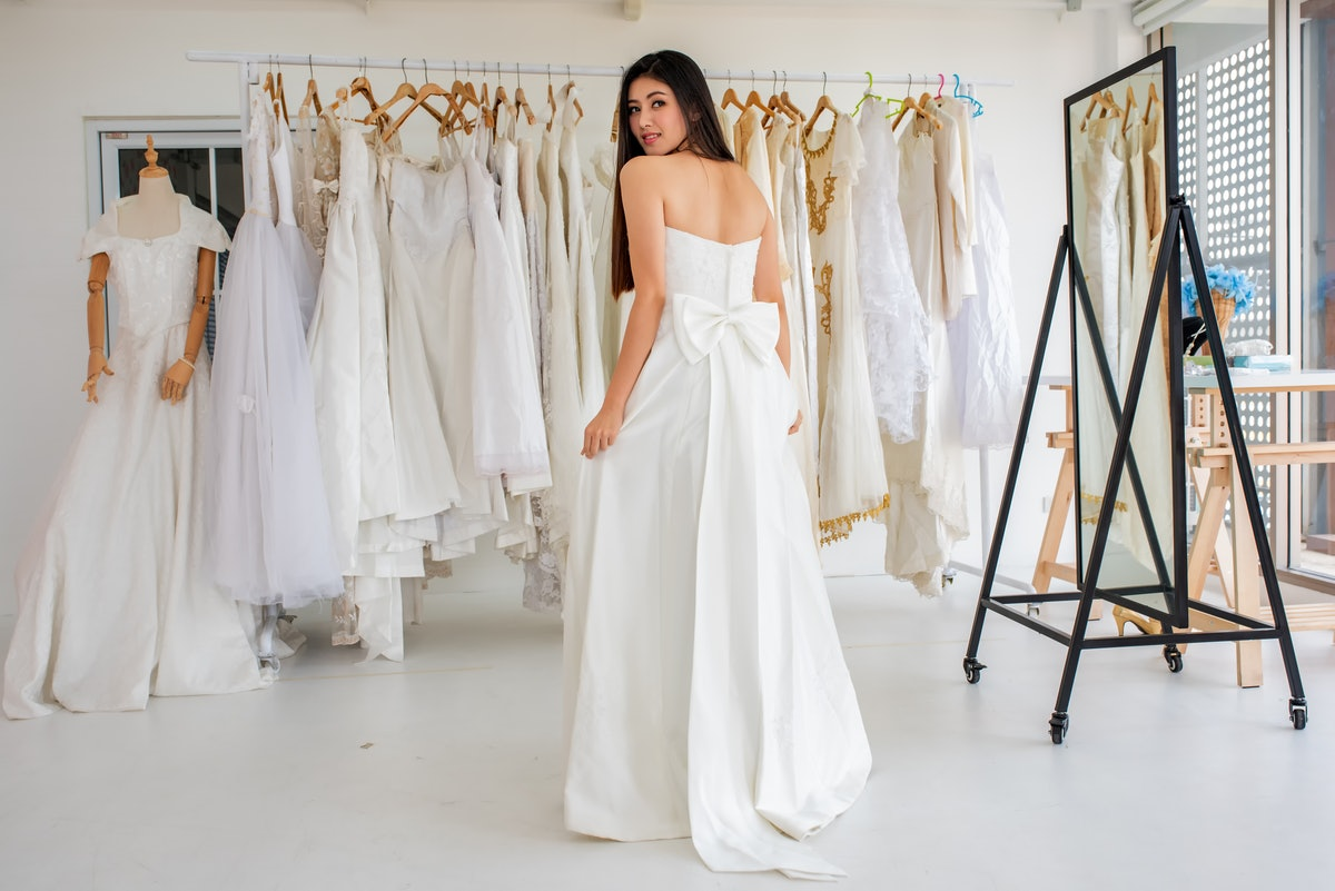 Young woman saying yes to the dress, trying on a gown before posting a picture on Instagram with a w...