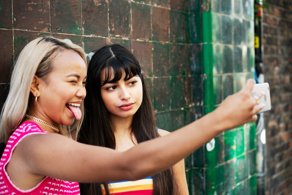 2 young women taking a fun selfie before posting on Instagram with birthday captions for best friend.