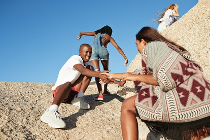 Young friends helping each other climb a rock before posting on Instagram with hiking puns, mountain...