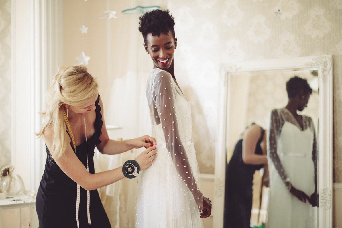 Young woman trying on her wedding dress before posting a pic on Instagram with a say yes to the dres...