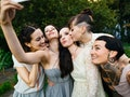 Bridesmaids taking a selfie with the brides before posting a pic on Instagram with wedding captions.