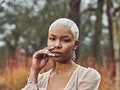 Young woman with platinum blonde hair, posing in a field before posting an Instagram with with a blo...