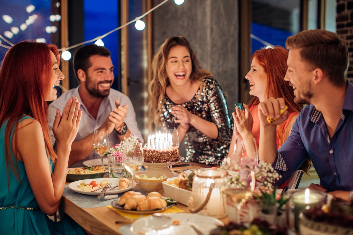 A group of friends posing around a birthday cake before posting on Instagram with a birthday cake qu...