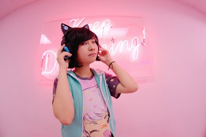 e.l.f.'s Game Up Contest winner Wren in an all-pink room anime shirt, and cat-eared headphones.