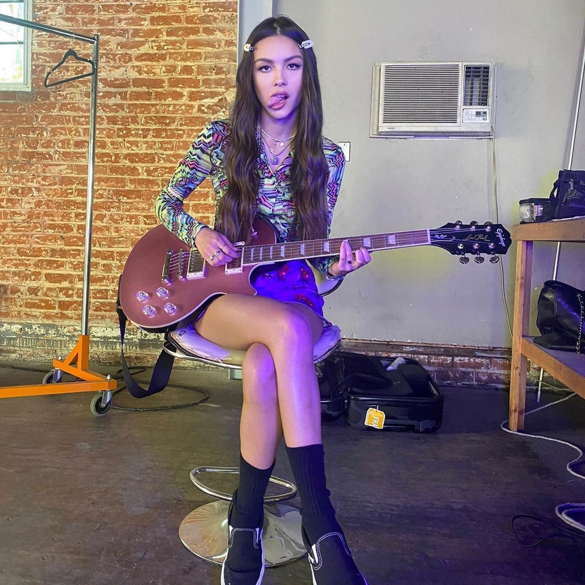 Olivia Rodrigo sitting on a stool holding a guitar and wearing a long-sleeve blouse, printed mini sk...